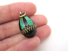 A lovely vintage guilloche enamel and genuine onyx egg pendant or fob charm. It has bold green and black stripes, with the gemstone cabochon on