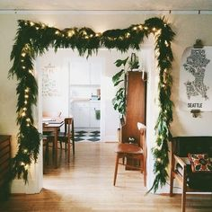 Lighted, evergreen garland around a doorway makes for a romantic transition between rooms in graphic designer and photographer Julia Manchik's home