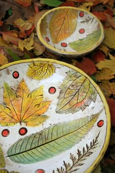 Ceramic bowls with leaf impressions. Dark brown underglaze wiped off remains in impressions.. Blended Underglaze fall colors. Clear gloss finish.