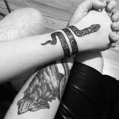 Creatively expressed snake tattoo wrapped around the wrist. Looks like a bracelet.
