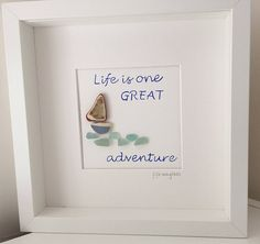 This picture depicts a little sea pottery boat sailing on a beautiful aqua coloured sea glass sea, with the message life is one GREAT adventure. The boat has a beautiful blue and white hull, with a glazed terracotta piece of pottery for its sail. The little aqua sea glass is beautifully