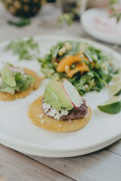 """""""easy version of sopes"""" made withfresh corn cakes, refried black beans, sliced avocado, crumbled cotija cheese and a squeeze of lime"""