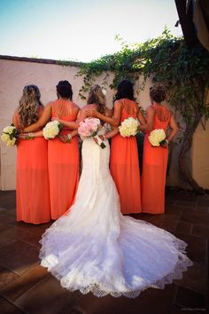 Bride with bridesmaids holding bouquets behind their backs