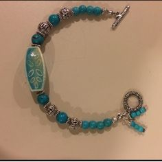 Turquoise bracelet This is a 7 1/2 inch bracelet made from turquoise and Tibetan silver. The center bead is a ceramic looking bead. Not sure exactly what it is made of. But it is gorgeous   Toggle clasp. Two little bead charms. Handmade by me. NWOT Jewelry Bracelets
