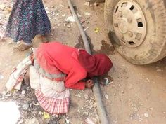 Yemen - child drinks from a leaking pipe