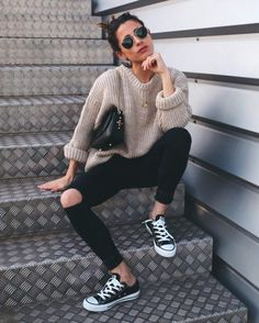 Maria Valdes is seen pairing black ripped jeans with a chunky knitted sweater, rolled at the sleeves, with black and white converse and a pair of circular framed shades. Sweater: Dylan Kain, Shoes: Converse.