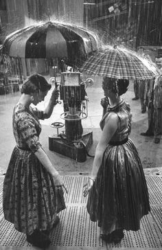 """Models demonstrating umbrellas under artificial rain on the TV program """"Home."""" Photograph by Ralph Morse. USA, March 1954."""