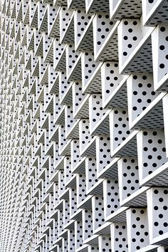 "Awesome Photography.   Awesome Design.   Wish I Knew More About This Building Would Love To Comment on Functionality & Harmony in Setting. I Like the implied ""Staircase"", ""Dominoes"" & ""Exagerated Perforations"" in The Geometric, almost M.C. Escher, Facade."