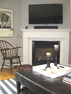 In this family room the existing paint colour was already perfect so we started to build the colour scheme around it. Notice the Windsor chair curled up at the fireplace is right at home. Open Shelving, Shelves, Round Ottoman, Glass Table, End Tables, Windsor, Paint Colors, Love Seat, Blinds