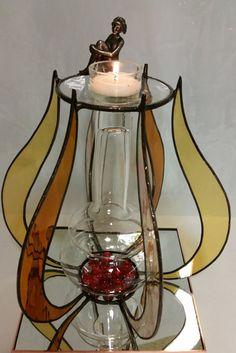 Vintage kaarsenstandaard met Tiffany glas in lood vlammen en een tinnen figurine bovenop badend in het kaarslicht. Een echte blikvanger.