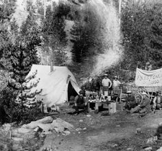 """Pikes Peak or Bust"" - View of men camping in (probably) Colorado, with a covered wagon, tent, dogs, horses, and liquor bottles. Lettering reads: ""Pikes Peak or Bust 1860."""