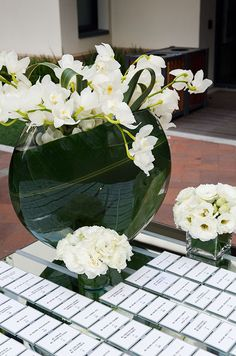 An elegant place card table features white ranunculus, orchids and roses in glass containers.