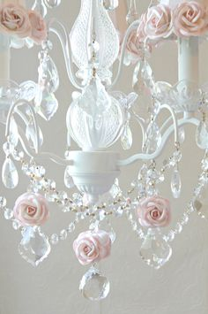 "Light up your room. With crystal prisms and pink dupioni silk shades, trimmed with matching mulberry roses in full bloom, the chandelier will dress any room with loads of sparkle, romance and charm. Perfect for a nursery, little girls bedroom, or breakfast nook. <BR><BR> • Cottage White<BR> • Handmade to order<BR> • Ready to hang <BR> • 13""W x 20""L<BR> • Comes with matching ceiling cap and 39"" of chain"
