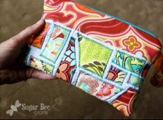 Using a zigzag stitch in a bright thread, sew smalls strips and scraps of fabric onto a background in a mosaic pattern to create the Scrappy Ticker Tape Clutch.