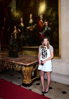 What a setting: The Avengers actress poses beside a piece of one of the stately home's impressive art collections