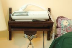 """The patent-pending CPAP """"Charlie"""" Shelf is a great way to store your CPAP machine and free up space on your bedside table. It is a wall-mounted unit that houses your CPAP machine and has a decorative hook for your mask."""