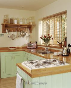 Gas hob in wooden worktop on peninsular unit in pastel green cottage kitchen with slatted wood blind. Add a farmhouse sink. And maybe more of a sage cabinetry and yes!