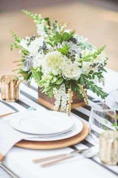 "Tables will feature natural wood boxes filled with cream hydrangea, peach and blush ranunculus, queen anne's lace, bay laurel, dusty miller, white lisianthus and 2- 4"" succulents."