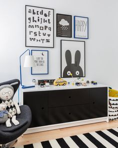 This child's black-and-white playroom features a striped rug, framed prints on the wall, and a large dark-gray dresser for convenient storage.
