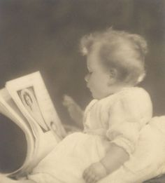 Princess Elizabeth by The British Monarchy, via Flickr-Princess Elizabeth (now The Queen) looking at pictures of her parents, 20 January 1927 by Marcus Adams  This photograph was taken during Princess Elizabeth's first sitting at the Children's Studio, following the departure of The Duke and Duchess of York on a six-month tour. She was given photographs of her parents to look at to keep their faces familiar whilst they were away.