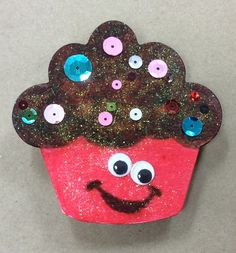 Shopkins Cupcake Magnet Clothespin craft I  made for AC Moore. Color with kids markers, add details with Sharpie marker. Apply white glitter glue over cupcake, it will not bleed with Sharpie, but will with kids markers. Add wiggle eyes and sequins to icing. Glue completed cupcake to clothespin. Glue good magnet to back of clothespin (not magnet tape!)