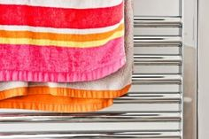 If simply hanging your towel over the edge of the shower door isn't enough, you may want to invest in a heated towel warmer. They are usually mounted to the wall, and will warm up your towel all the while that you are in the shower. Bathroom Heater, Towel Radiator, Towel Warmer, Bob Vila, Heated Towel Rail, Simple Bathroom, Shower Doors, Bathroom Inspiration, It Is Finished