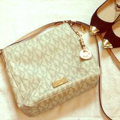 Michael Kors Jet Set Vanilla Crossbody Used a few times, purchased from MK, comes with dustbag & have box. Vanilla messenger bag with tan leather trim and gold toned hardware. Zip top closure with 1 exterior slip pocket on back with snap closure. 1 interior zip lock and 4 interior slip pockets. Adjustable leather shoulder strap. No visible wear on outside or inside except scratches on the gold emblem & blue reside on inside key hook, which won't come up in pictures. 10 by 9.5 inches. Ask…