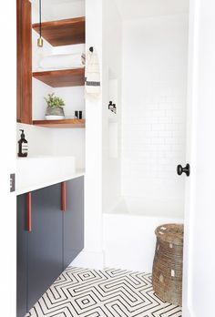 Pattered floor tile with wood shelves in a bathroom