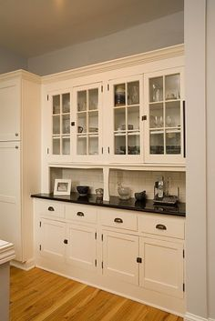 Row of closed cabinets at bottom. Row of glass cabinets at top. Stone countertop.
