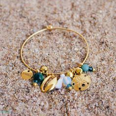 """At the Seaside is inspired by the colours and seashells found at the beach. The bangle features a cowrie shell, which has deep symbolism in many cultures and dates back to ancient times and resembles wealth and prosperity. The sand dollar charm represents the 5 essential elements of life; radiance, freedom, nature, beauty and peace, and is often referred to as the 5 white sand dollar doves. The bangle also includes opalite, amazonite and chrysocolla stone beads on a 22k gold plated bangle."""""""