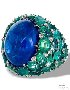 18k white gold cocktail ring features a 26.09 ct. oval-shape tanzanite cabochon center, with a setting decorated in 9.37 cts. t.w. emeralds and 0.76 cts. t.w. diamond accents.