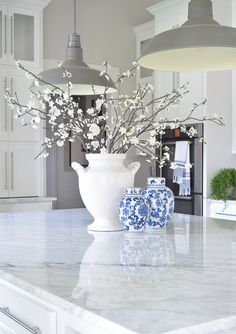 cozy and inviting home with blue and white ginger jars white blossoms white carrar marble white cabinets white farmhouse Kitchen Island Centerpiece, Kitchen Island Decor, Home Decor Kitchen, White Farmhouse Kitchens, Farmhouse Decor, Blue Centerpieces, Inviting Home, White Vases, Ginger Jars