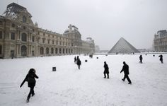 ~Paris~ People stroll in the snow covered square of the Louvre museum, after a snowfall in Paris, Sunday, Jan. 20, 2013. (AP Photo/Christophe Ena