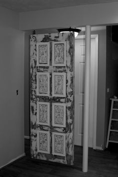 Re-claimed door as a screen to hide our bathroom. I sanded the door to the finish you see and hung it on stainless steel eye hooks. I hand aged the hooks with sandpaper and brown Rustoleum texture paint to fit the feel of the door.