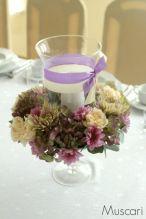 Szklany lampion ze świecą i fioletowymi ślubnymi kwiatami