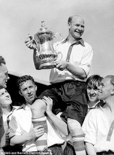 Charlton Athletic's Bert Johnson (r) looks up at captain Don Welsh (c) as he shows off the FA Cup whilst being carried shoulder high by triumphant teammates Jack Shreeve (second l) and Peter Croker (second r) after the 1947 win over Burnley