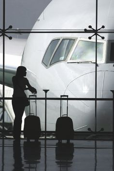 this picture is amazing. i love how big the plane is and how she is a silhouette against the white plane. i love how its composed and the rule of thirds it creates