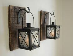 Overall size: Each board is approx. 5 x 9.5 inches . Lanterns are 4x4 inches square and 7 inches tall with the handle extended.  Gorgeous, unique and one-of-a-kind! Two black metal and glass lanterns each hanging from a wrought iron hook that is mounted to a recycled wood board.  Looks great on each side of a doorway or window. Add small pumpkins for Fall, or some greenery for the Christmas holiday. So many uses!  *******See photo #5 for all available colors (using our painted mason jar…