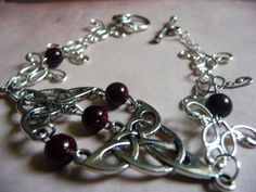 This beautiful bracelet is made up of silver Celtic knot work designs and embellished with gorgeous deep burgundy glass beads. The beautiful swirling designs make this piece a true treasure. This bracelet fastens with a silver rose toggle clasp. This would be a great piece to wear with any formal attire or even a casual outfit that you want to spice up a bit.  www.etsy.com/shop/natureslace  www.facebook.com/natureslace