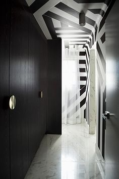 black and white graphic ceiling and wall treatment in a hallway with hidden closets