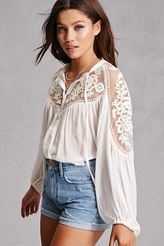 A delicate crepe woven top featuring a sheer mesh-paneled yoke and sleeves with floral crochet accents, a buttoned front with a self-tie at the neckline, long self-tie puff sleeves, and a billowy silhouette. This is an independent brand and not a Forever 21 branded item.