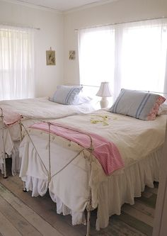 pretty guest room - love the iron beds and chippy painted floor