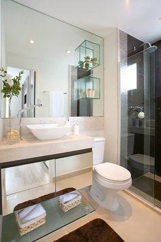 Banheiro suíte casal em tons de bege e marrom. Nichos de vidro no espelho. Móvel com porta de espelho. Pastilha Marrom. Banho. Bancada em mármore travertino.
