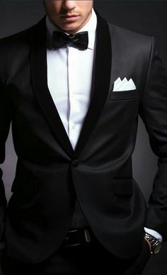 Black tuxedo, white dress shirt, and black bow tie with white pocket square and black belt.