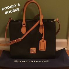 DOONEY & BOURKE  Black/Natural Leather Excellent Condition!!!  Very Classy!!!  Still had the wonder smell of leather, only carried a few times. Classy Black that will go with everything and every season. Natural leather dual double rolled handles and adjustable/adjustable Crossbody strap. D&B logo plate on front also luggage tag, gold tone hardware also metal feet to protect button of bag. Signature fabric, key holder. Zip pocket w/wide slip pocket underneath, 2 slip pockets on other side…