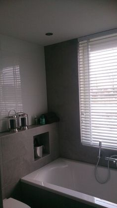 Mijn nieuwe badkamer met grijze en glans witte tegels, nis in bad en brede jaloezien voor het raam.