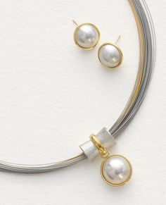 Orbit Pendant & Mabe Pearl Earrings by Gabriel Ofiesh. These pieces possess the timeless beauty of pearls, gold and sterling silver. Necklace has a 14mm white mabe pearl pendant and a ring of 18k gold that revolves freely around a sterling silver bead. Stainless steel and gold-plated 75-strand neck coil. Earrings have 12mm white mabe pearls set in 18k gold with sterling silver backing and 14k gold posts.