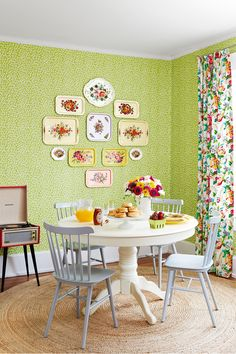 Cultivate an indoor vertical garden with a green rambling vine wallpaper. The small-scale pattern provides a muted enough backdrop for bolder statement pieces, like vintage metal trays featuring bold buds. A quartet of soft gray Windsor chairs and an heirloom-worthy pedestal table balance the pattern play on the walls.   - CountryLiving.com