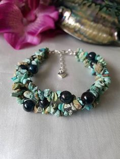 This is a gorgeous natural ladies gemstone bracelet. It is made using genuine turquoise rough nugget which has amazing natural colour and the contrasting polished apatite rounds. Perfect for summer days and beach holidays. Three strands are braided together to make a chunky but lightweight bracelet. This ladies jewelry is finished with a silvertone lobster claw clasp and it also has an extender chain with heart charm. Length is 7.5 inches (19cm) Extender 1.5 inches (4cm)
