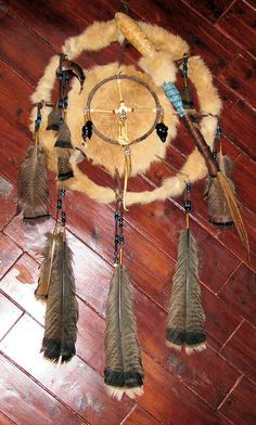 Rabbit fur medicine shield with dream catcher, gourde rattle, and faux bear claw. Bronze turkey feathers and brass cones. Muskrat jaw, coyote tooth, raccoon penis bone, turtle claw, obsidian arrowheads, quartz crystal.